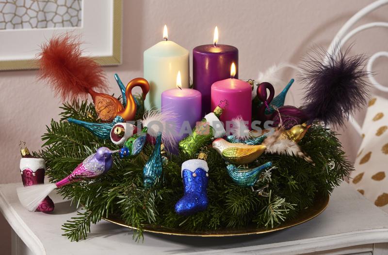 Glamourfaktor: Tannenkranz mit bunten Kerzen, Stiefelanhängern und Dekovögeln mit Glitter und Federschmuck