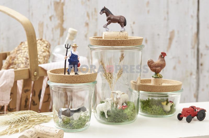 Basteln mit Korkuntersetzern - Weckgläser mit Moos, Ähren und ländlichen Figuren dekorieren. Als Deckel dienen Flaschenuntersetzer aus Kork